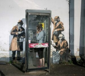 One of Banksys best known works of three men wearing sunglasses and using listening devices to snoop on a telephone box near GCHQ in Cheltenham